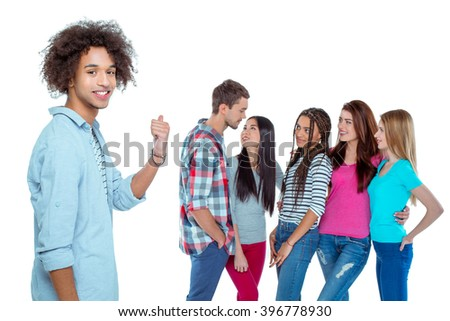 Studio shot of nice young multicultural friends. Beautiful people chatting. Focus on african boy. He looking at camera, pointing at friends and smiling. Isolated background - stock photo