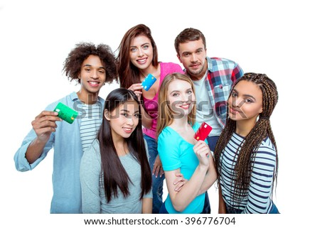 Studio shot of nice young multicultural friends. Beautiful people holding credit cards, looking at camera and smiling. Isolated background - stock photo