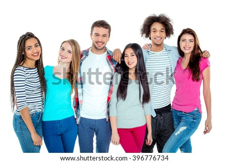 Studio shot of nice young multicultural friends. Beautiful people looking at camera, hugging and smiling. Isolated background - stock photo