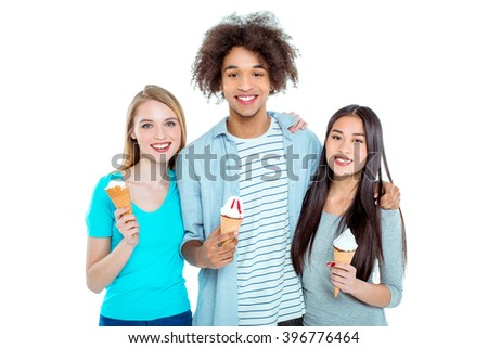 Studio shot of nice young multicultural friends. Beautiful people looking at camera, smiling and holding ice-creams. Isolated background - stock photo