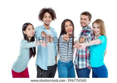 Studio shot of nice young multicultural friends. Beautiful people looking at camera, smiling and pointing at camera. Isolated background - stock photo