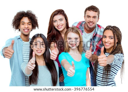 Studio shot of nice young multicultural friends. Beautiful people showing thumbs up, looking at camera and cheerfully smiling. Isolated background - stock photo