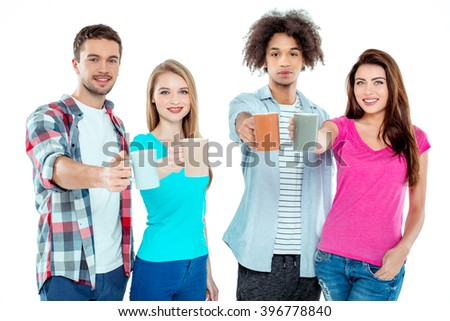 Studio shot of nice young multicultural friends. Beautiful people with cups of coffee looking at camera and smiling. Isolated background - stock photo