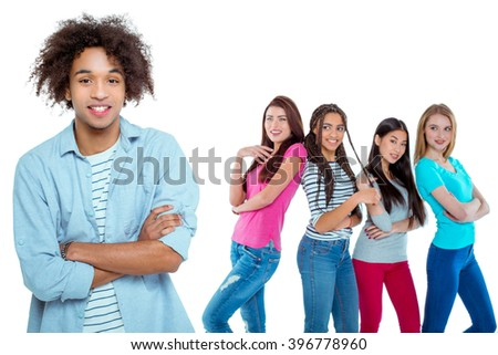 Studio shot of nice young multicultural people. Beautiful girls chatting and looking at young man. Focus on african boy. He looking at camera and smiling. Isolated background - stock photo