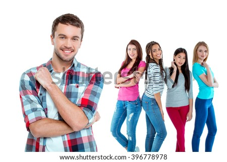 Studio shot of nice young multicultural people. Beautiful girls chatting and looking at young man. Focus on boy. He looking at camera and smiling. Isolated background - stock photo