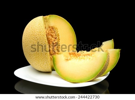 Studio shot of notched ripe melon galia with slices on plate isolated on black background - stock photo