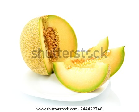 Studio shot of notched ripe melon galia with slices on plate isolated on white background - stock photo
