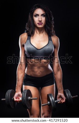 studio shot of perfect body of bodybuilder female with dumbbels; sexy muscular fitness woman on black background and with gym equipment; - stock photo