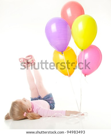 studio shot of pretty  little girl laying on the floor with balloons - stock photo