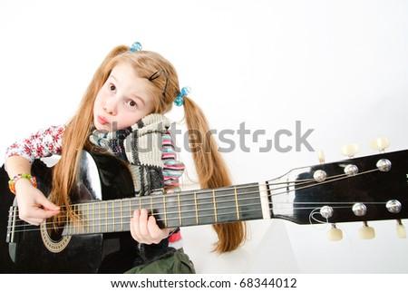 studio shot of pretty little girl playing black acoustic guitar - stock photo
