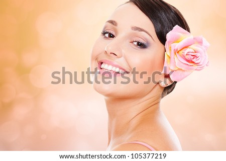 studio shot of pretty smiley model with rose in hair