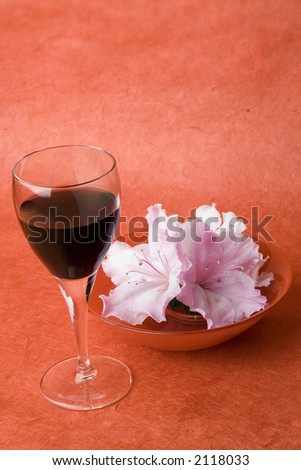 Studio shot of red wine in a wine glass with red glass bowl of a few azalea flowers. Shot against a red textured background.