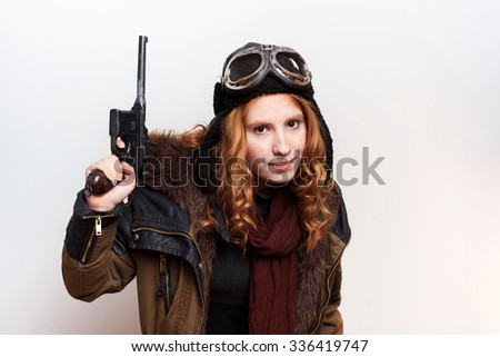 studio shot of redhead girl with vintage gun on white background
