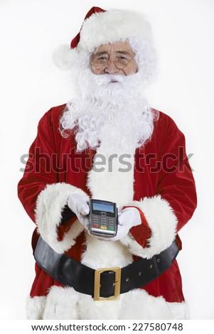 Studio Shot Of Santa Claus Holding Credit Card Reader - stock photo