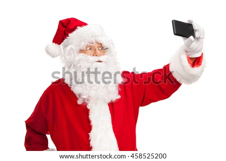 Studio shot of Santa Claus taking a selfie with a cell phone isolated on white background - stock photo