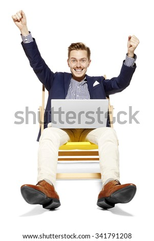 Studio shot of satisfied young man sitting on sunbed. He raises his arms in a gesture of victory. - stock photo