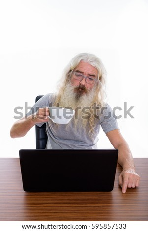 Studio shot of senior bearded man holding coffee cup while looking at laptop on wooden table