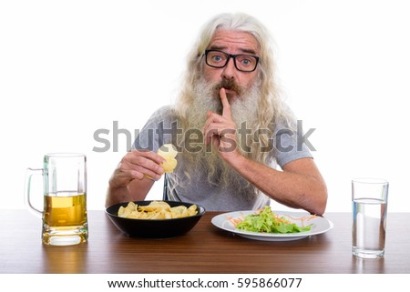 Studio shot of senior bearded man holding potato chips while shushing with healthy and unhealthy foods on wooden table
