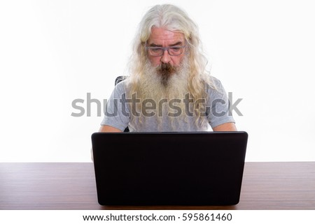 Studio shot of senior bearded man using laptop on wooden table