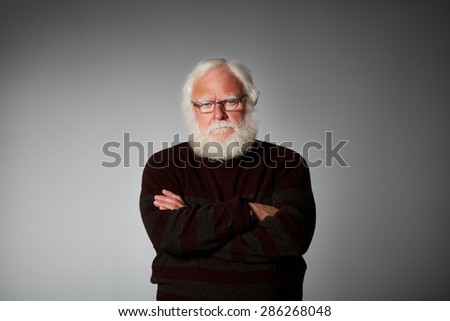 Studio shot of senior man standing with his arms crossed looking upset against grey background - stock photo