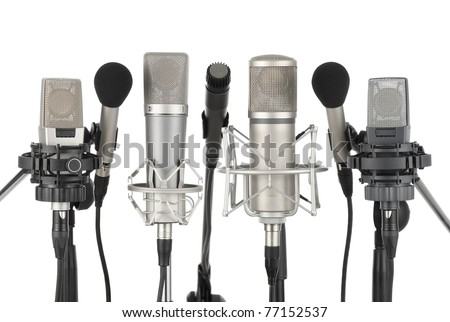 Studio shot of seven professional microphones in a row on white background - stock photo