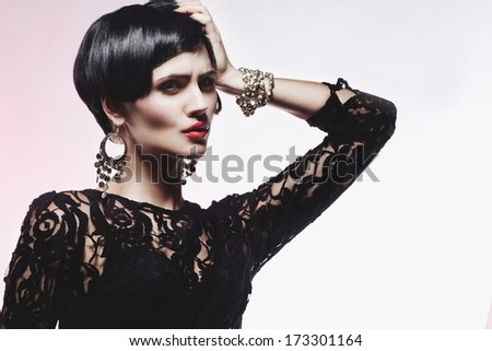 Studio shot of Sexy Fashion Woman in Black Dress and jewelry. Professional Makeup and Hairstyle