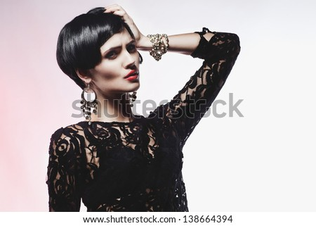 Studio shot of  Sexy Fashionl Woman in Black  Dress. Professional Makeup and Hairstyle