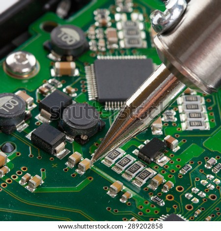 Studio shot of soldering iron with microcircuit - stock photo