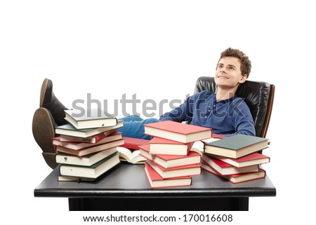 Studio shot of student having a rest with the legs on the desk, daydreaming among piles of books, isolated over white background