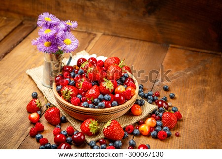 Studio shot of summer berries on wooden background - stock photo