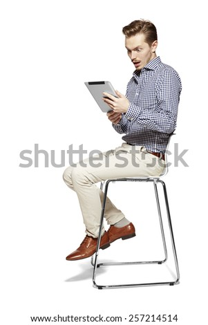 Studio shot of surprised man looking at tablet. - stock photo