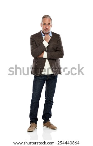 Studio shot of thoughtful mature man in casual wear looking at camera over white background - stock photo