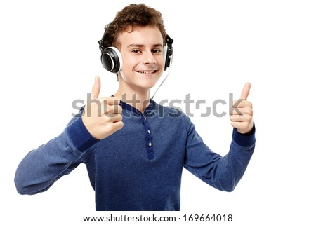 Studio shot of trendy teenager listening to music at headphones and making the thumbs up sign, isolated over white background - stock photo