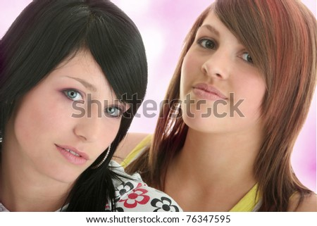 Studio shot of two beautiful happy young woman (sisters)