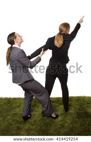Studio shot of two business women standing on grass, having a disagreement. wanting to take a different path