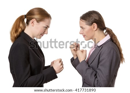 Studio shot of two business women with their fists raised, ready for a fight. Isolated on White.