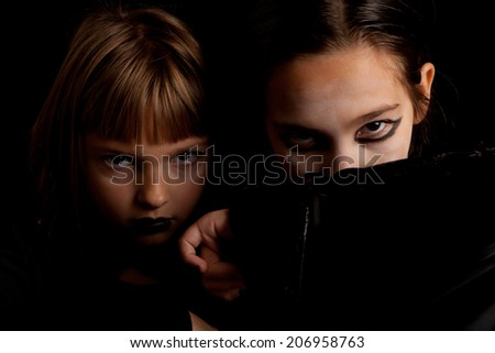Studio shot of two little girls dressed as vampires looking serious for Halloween