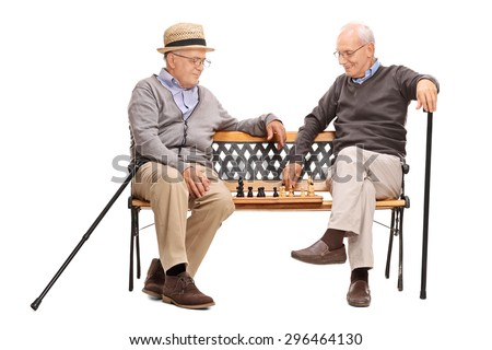 Studio shot of two seniors playing a game of chess seated on a wooden bench isolated on white background - stock photo