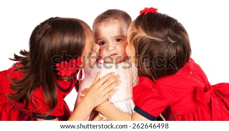 Studio shot of two young girls kissing their baby sister who does not appear to enjoy it. - stock photo