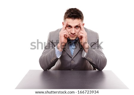 Studio shot of unhappy businessman sitting at desk with hands on forehead, isolated over white background - stock photo