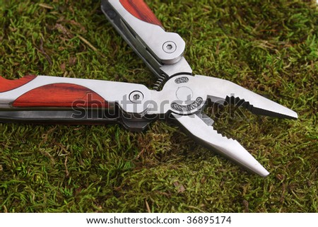 Studio shot of utility knife with pliers laying on grass