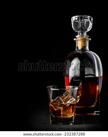 Studio shot of whiskey in a carafe and glass isolated on black  - stock photo