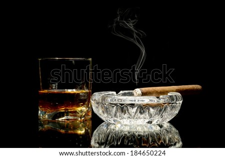 Studio shot of whisky in a glass and a cigar in ashtray isolated on black - stock photo