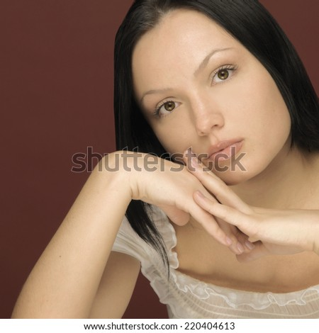 Studio shot of woman leaning face on hands