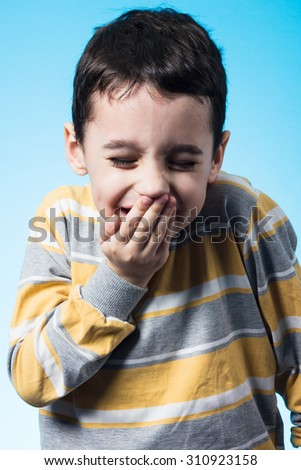 Studio shot of 5 years old boy covering his mouth with his hand. - stock photo
