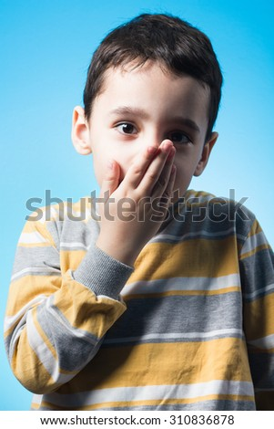 Studio shot of 5 years old boy covering his mouth with his hend. - stock photo