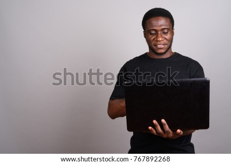 Studio shot of young African man wearing black shirt against gray background