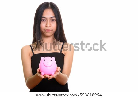 Studio shot of young Asian teenage girl holding piggy bank isolated against white background