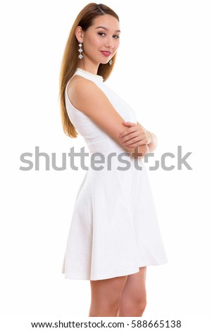 Studio shot of young beautiful Asian woman standing with arms crossed