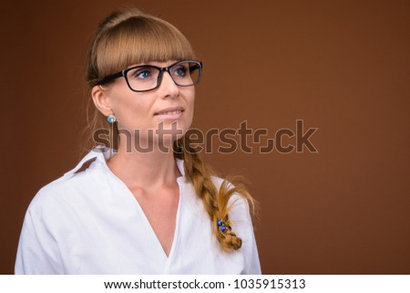 Studio shot of young beautiful businesswoman against brown background